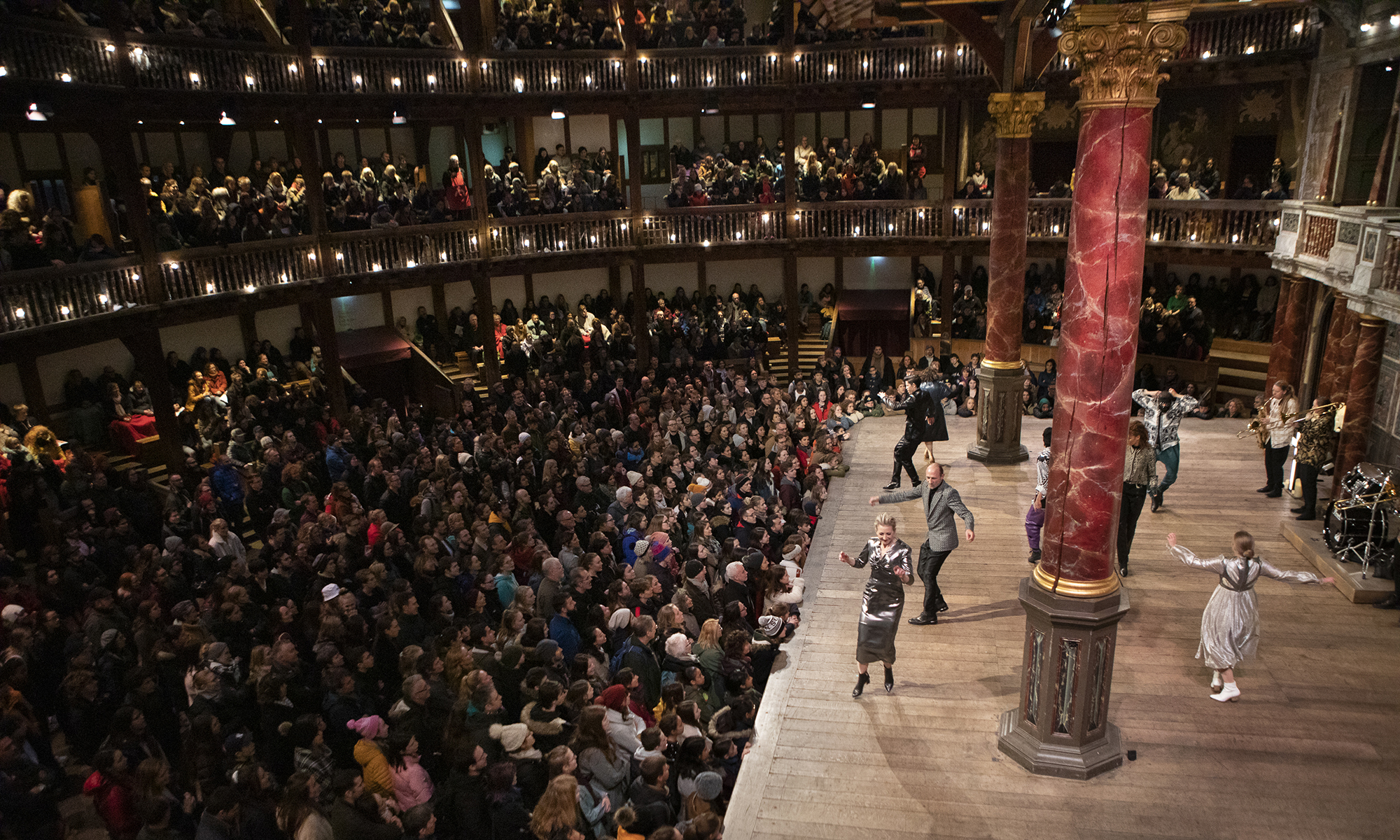 Actors dance on a wooden thrust stage, whilst a sea of audience members stand and watch.