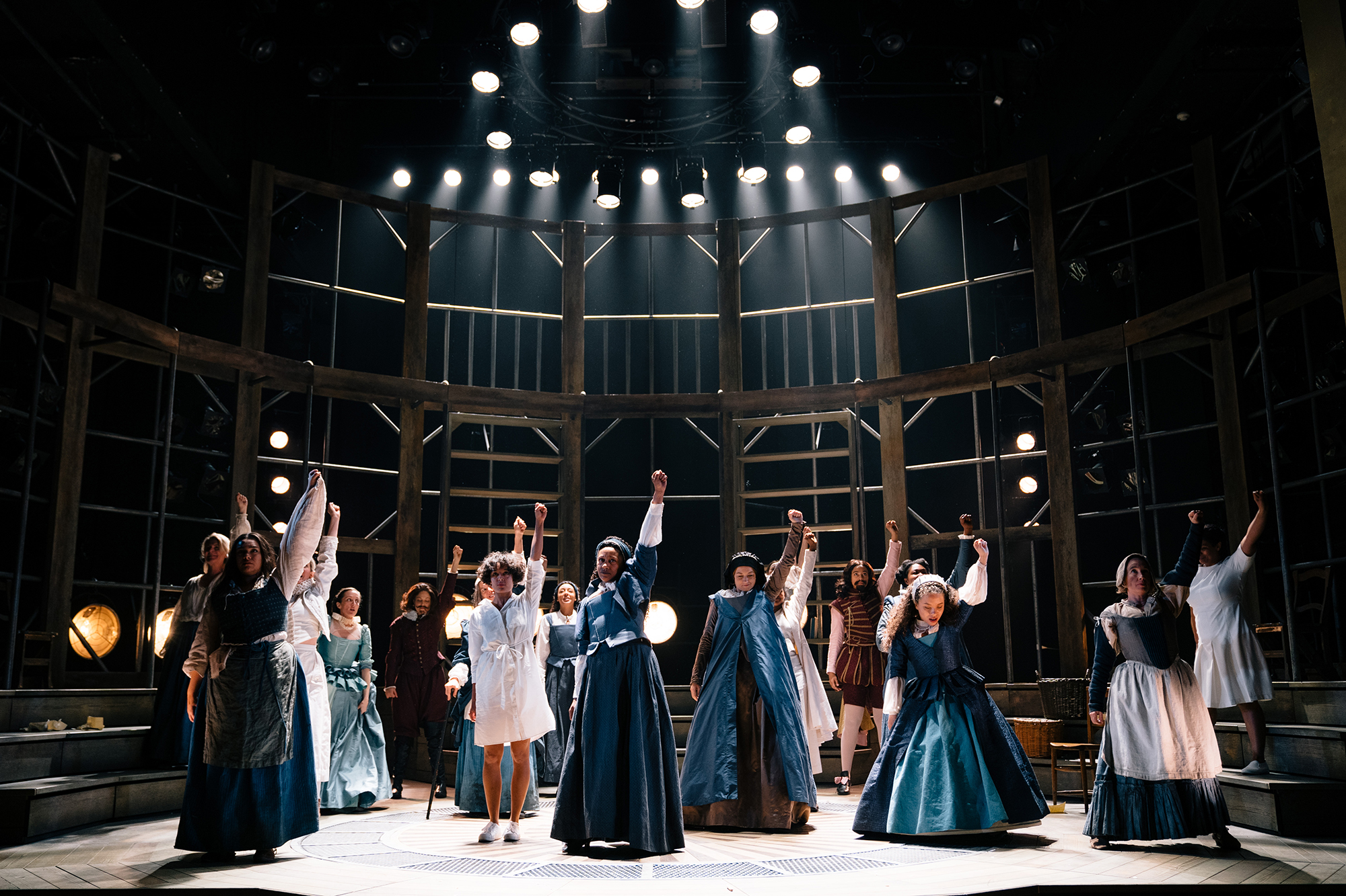 A group of actors stand on stage under spotlights, their left arms raised in the air into a fist.