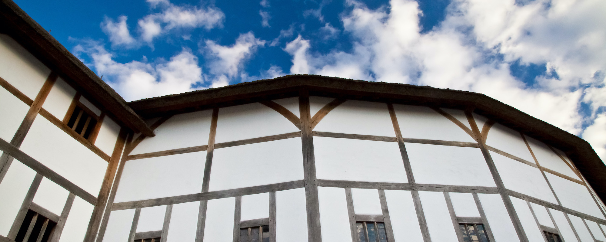 A timber-framed building in front of a blue sky
