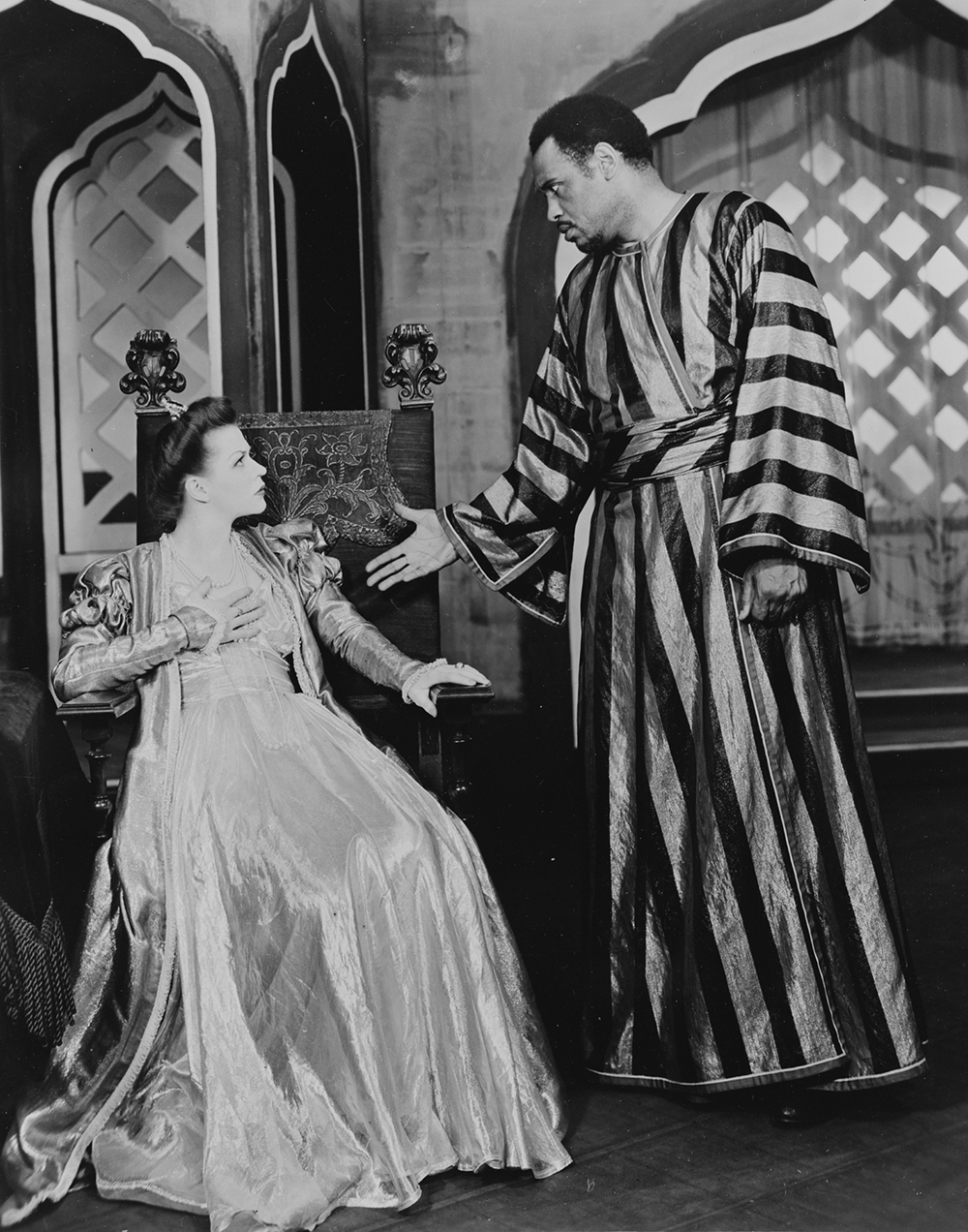 A black and white photograph of a woman sat in a chair, wearing an elaborate gown, with a man reaching out his hand next to her.