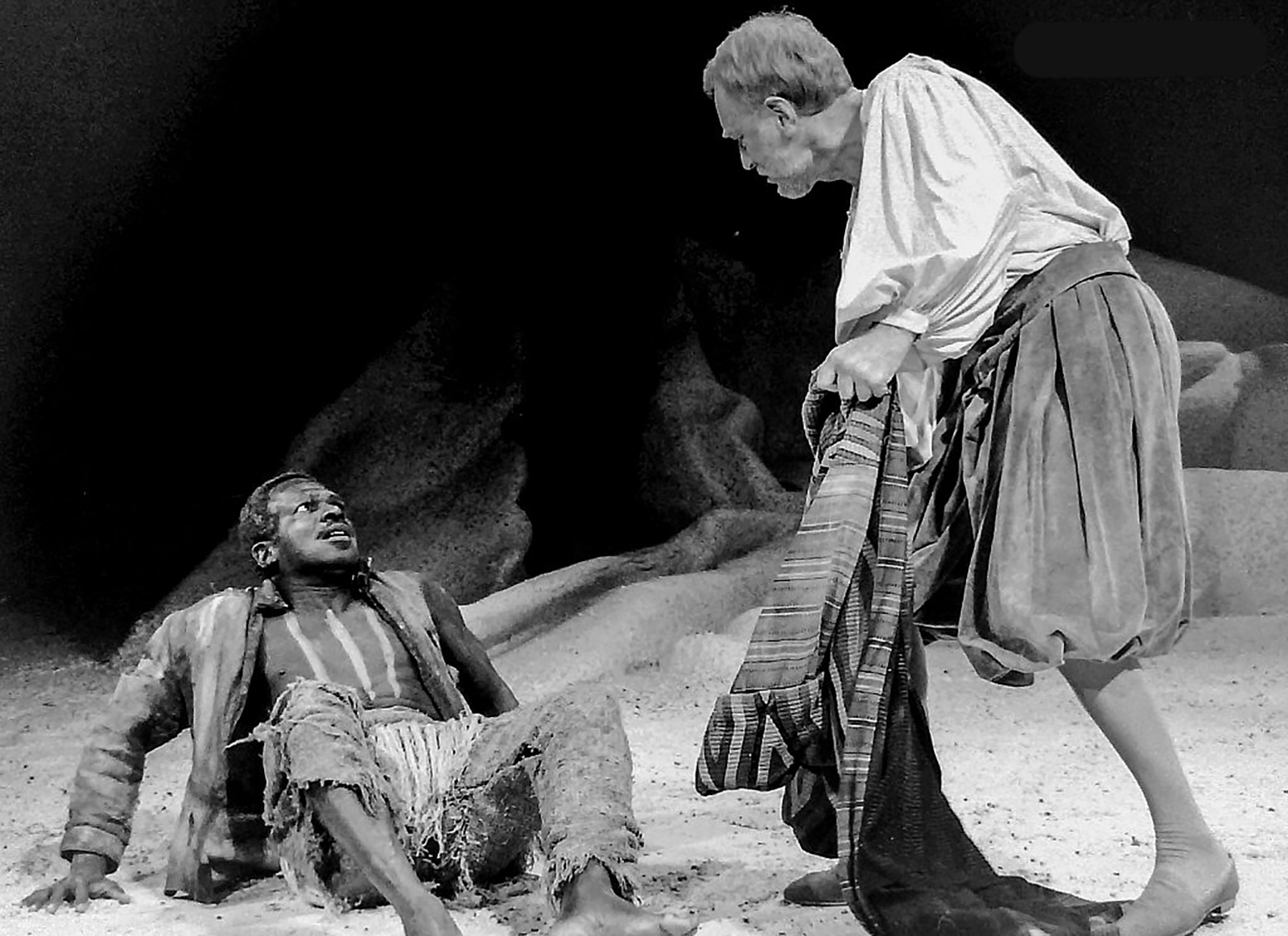 A man sits on the floor, leaning back on his hands, staring fearfully at another man looming over him.