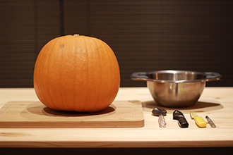 A pumpkin sits on a board next to a bowl and a series of knives.