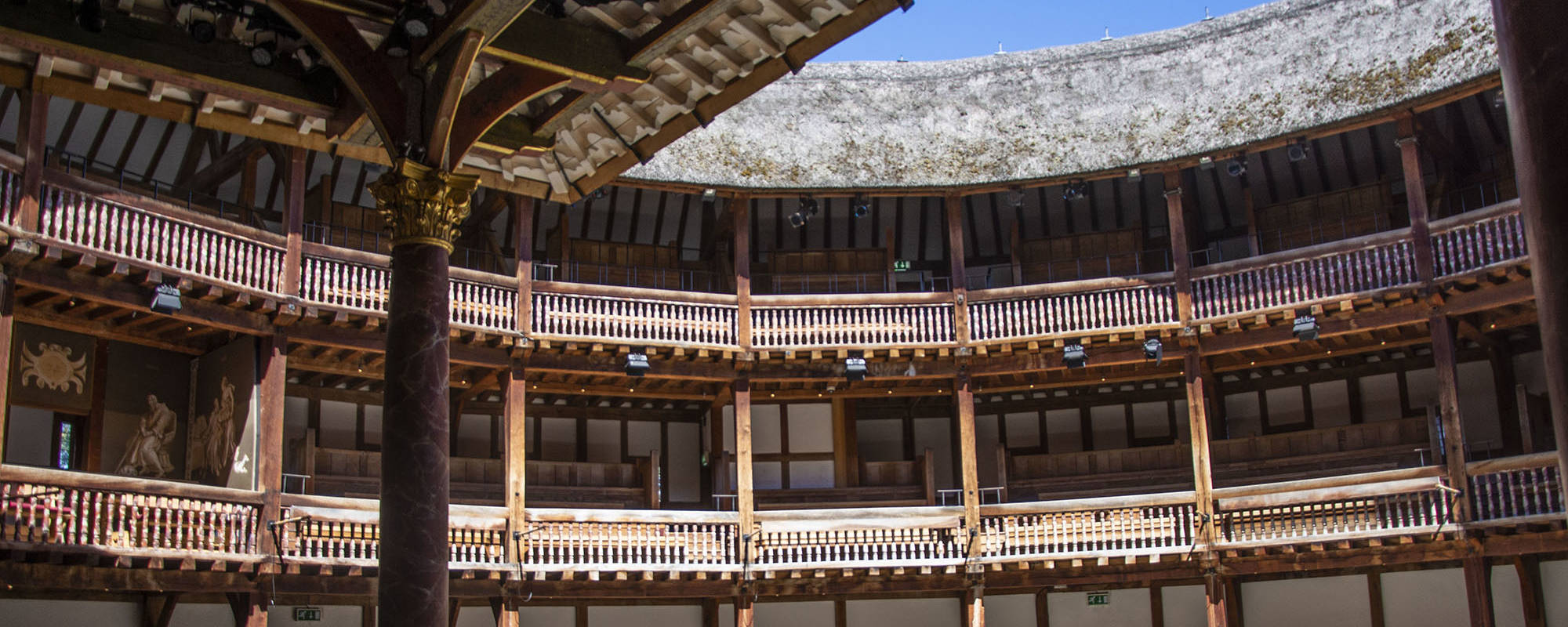 Sunlight streams into the yard of a wooden circular theatre.
