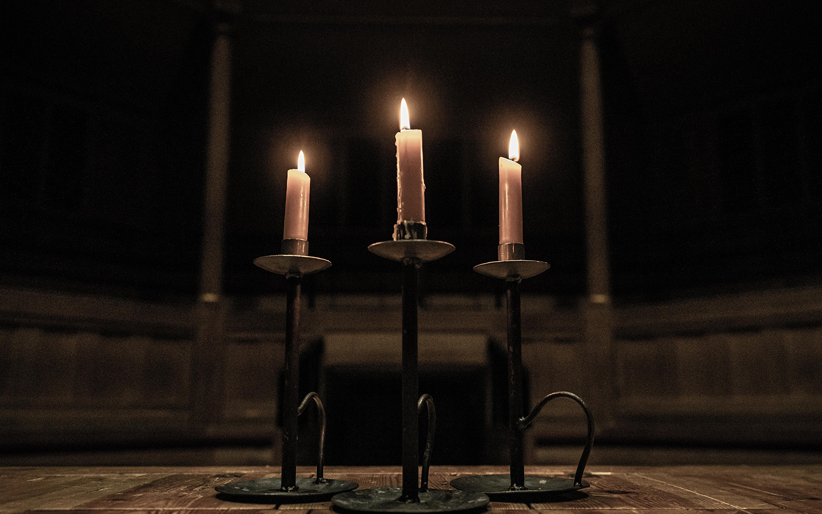 Three lit candles in the dark shadows of an indoor wooden theatre.