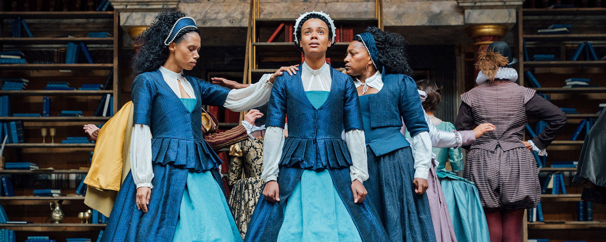 Three women, wearing similar blue Elizabethan dresses, stand together, each resting a hand on the other, supportive.