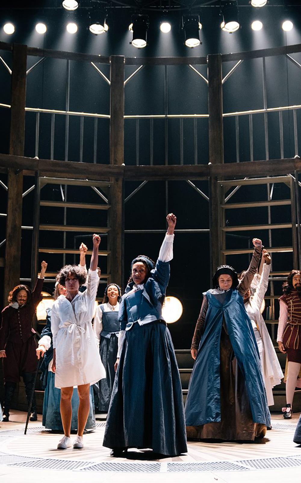 A group of women hold their fists in the air on a dramatically lit stage
