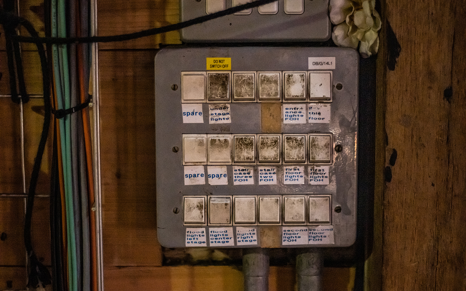 A grey electrical box, with lightswitches covered in homemade labels