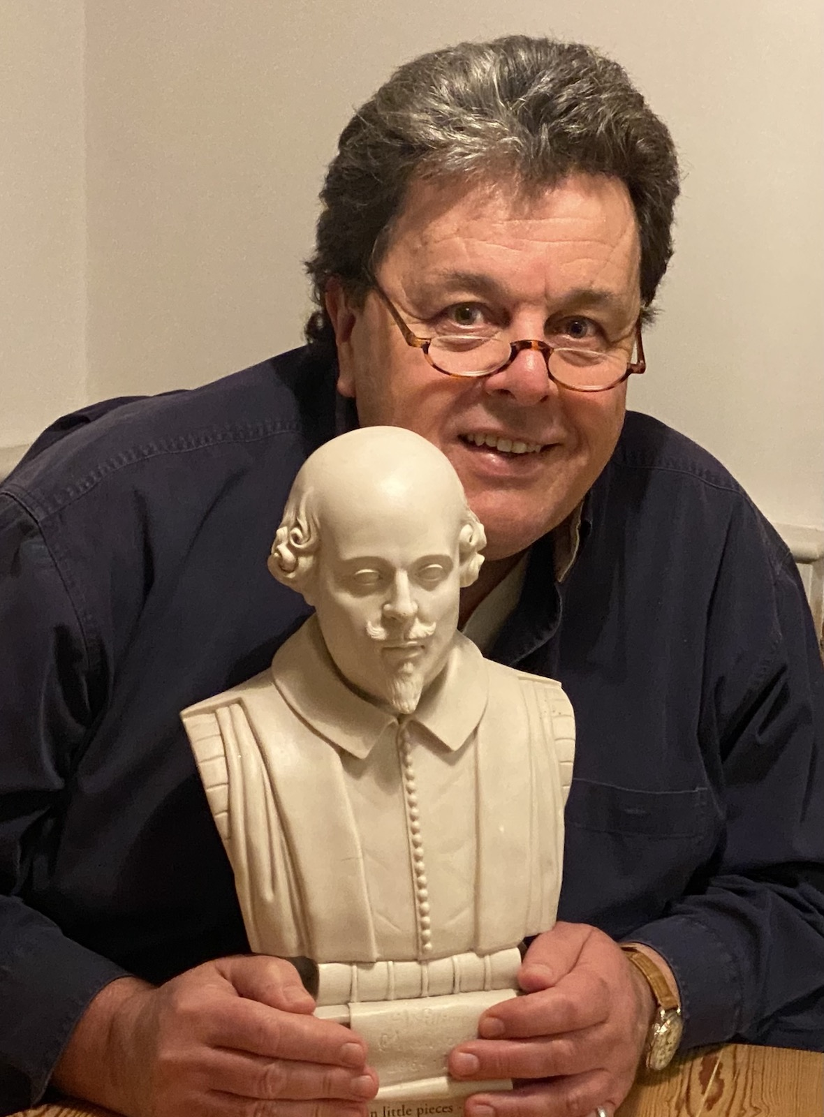 A man holding a small bust of Shakespeare's head