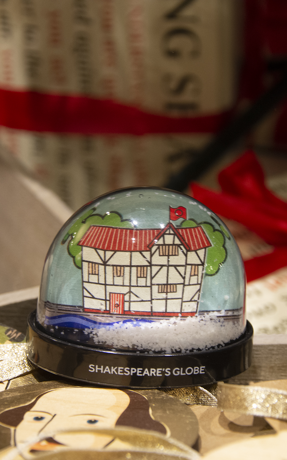 A snowglobe with a cartoon of a round wooden theatre as its background