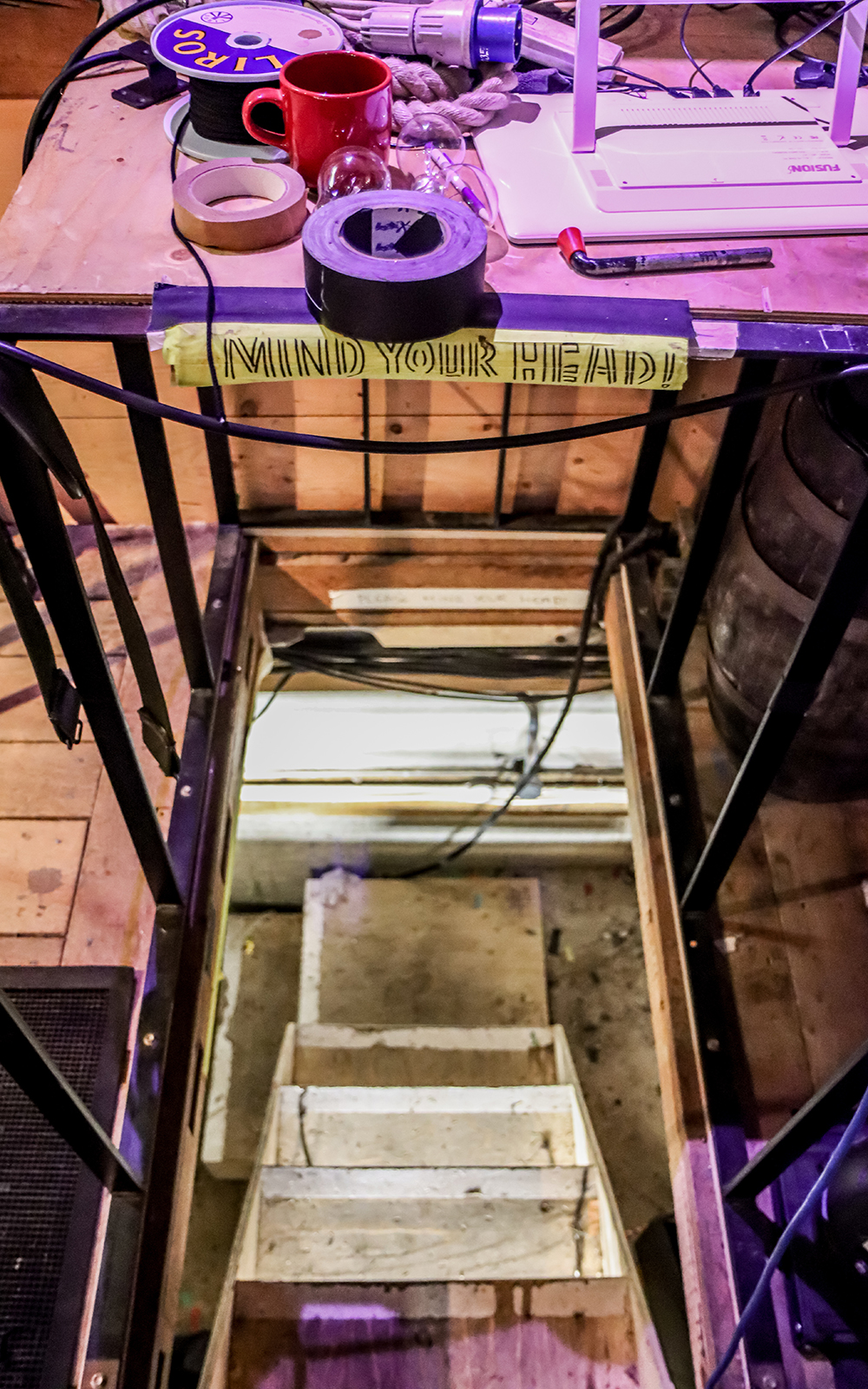 A narrow, steep staircase leads down to a basement, with a 'mind your head' sign above it