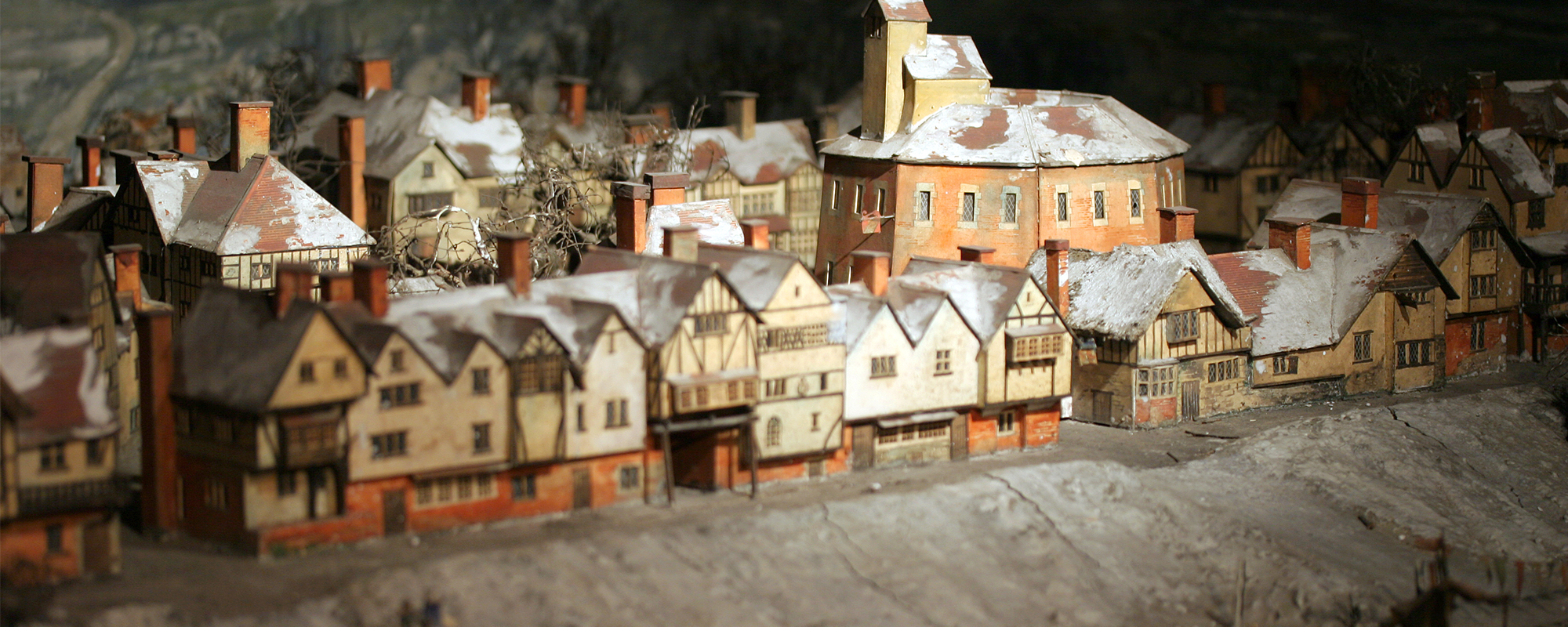 A model box of a wooden circular theatre surrounded by smaller Tudor buildings, along the bank of a snowy and frozen River Thames.