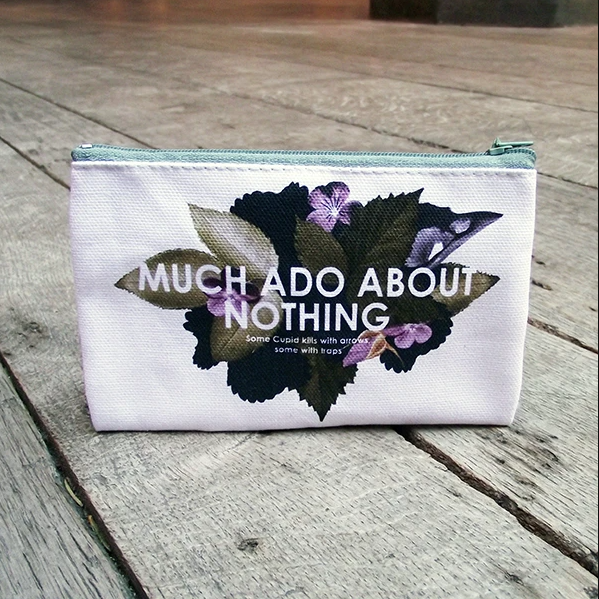 A white cloth purse with floral design and text reading: Much Ado About Nothing