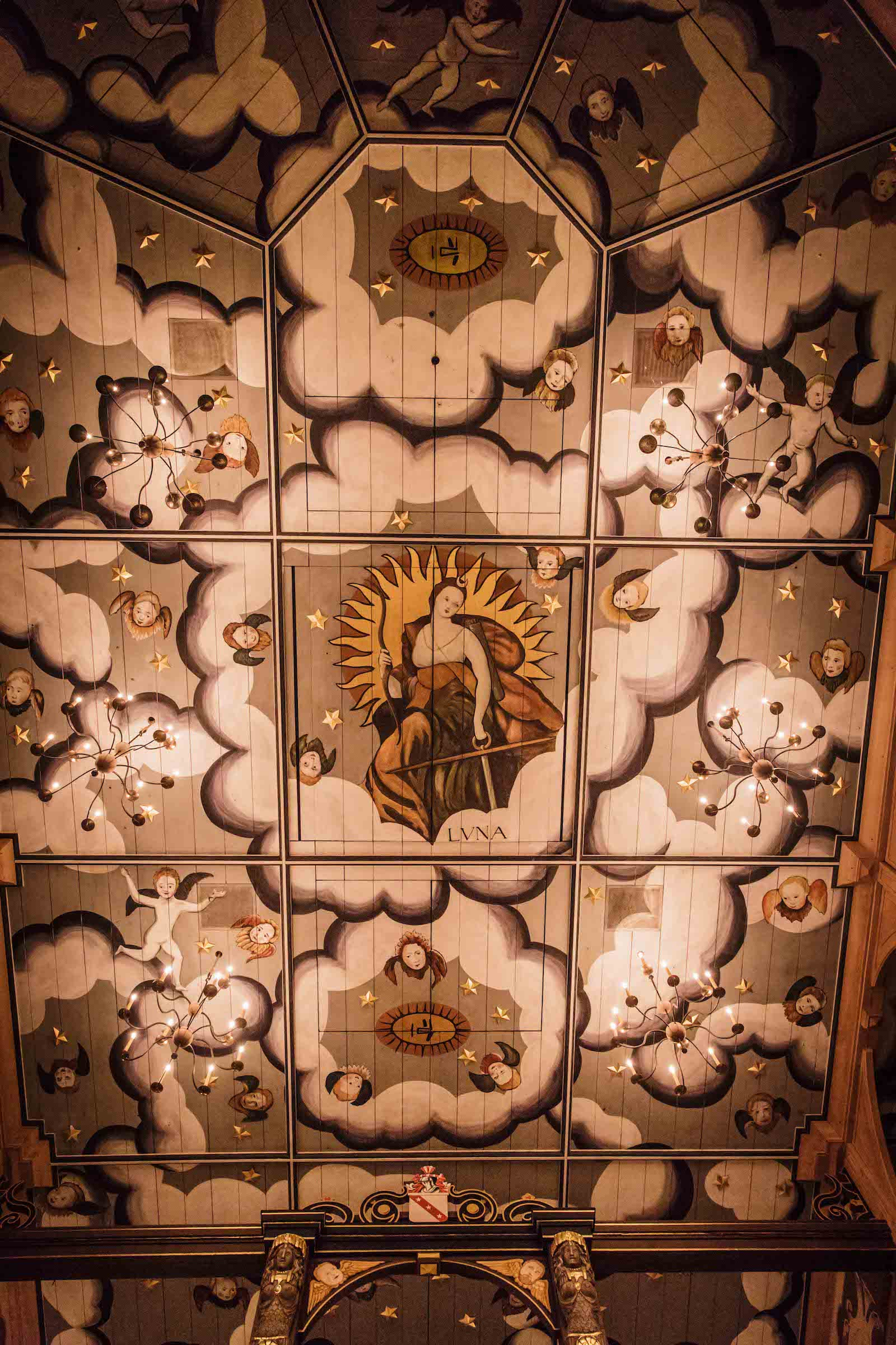 An intricately painted ceiling, looking up at it from below, with illustrations of clouds and angels