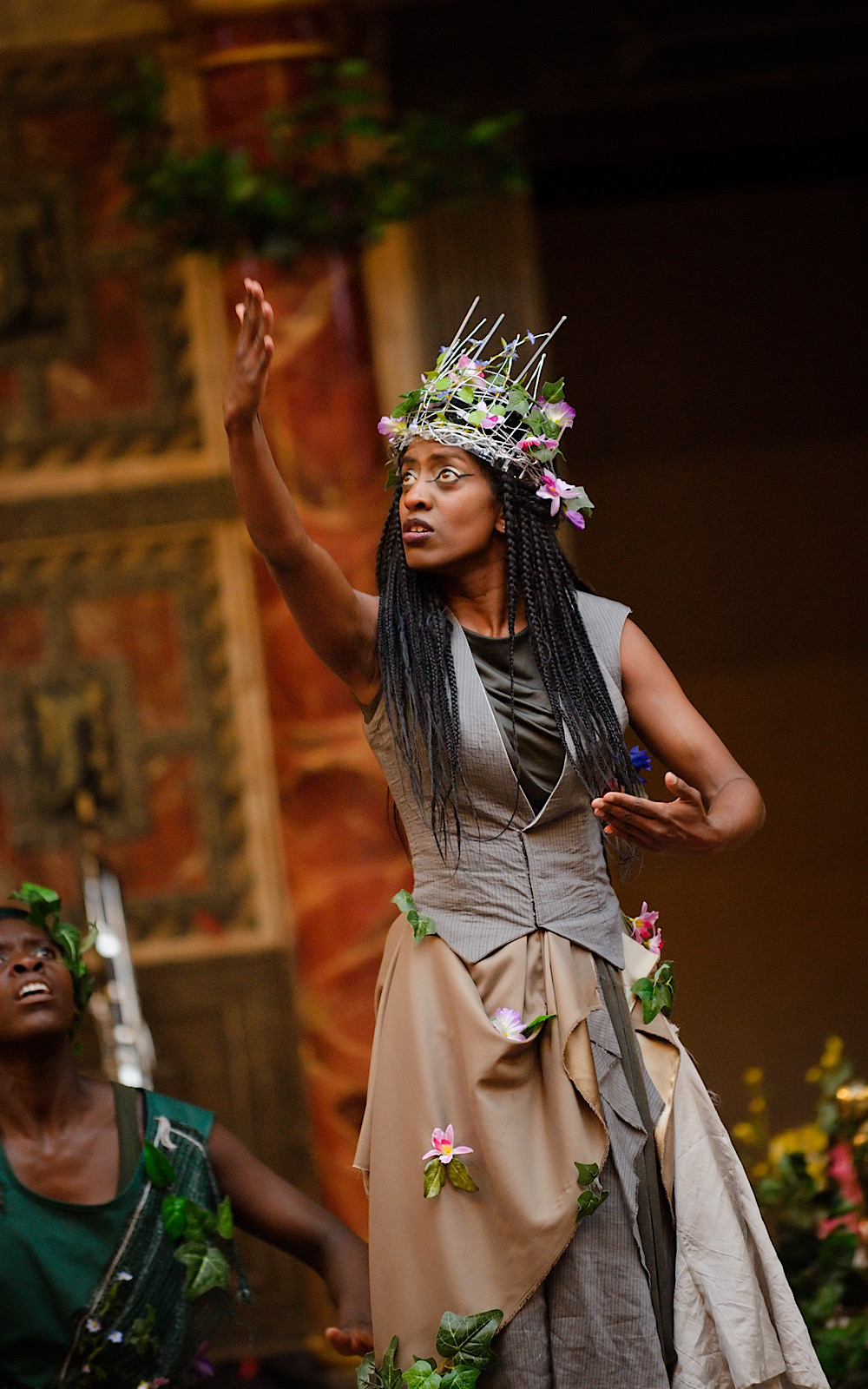An actor performs on stage wearing a crown of flowers, with one arm lifted in the air