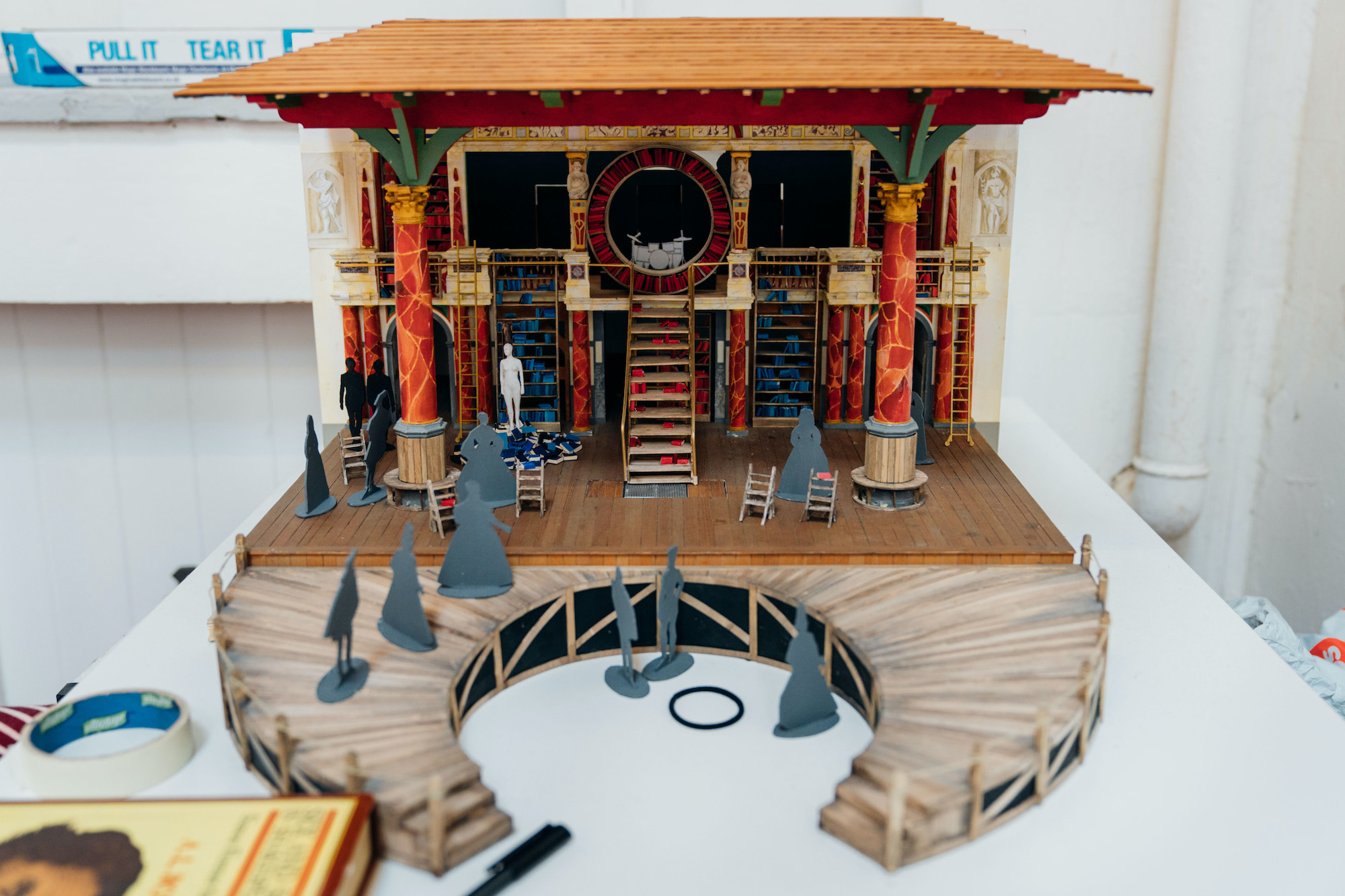 A mini set of a theatre which shows a wooden roof, wooden stage, steps, pillars and cardboard cut-out characters