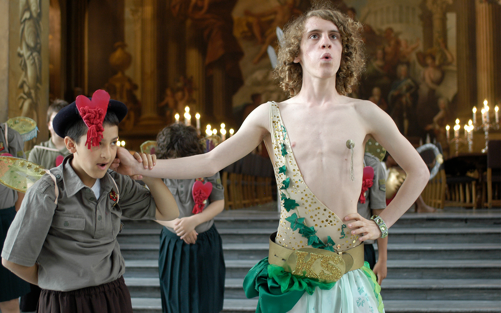 An actor dressed in a gold leotard and green skirt has his hand around the neck of a young actor