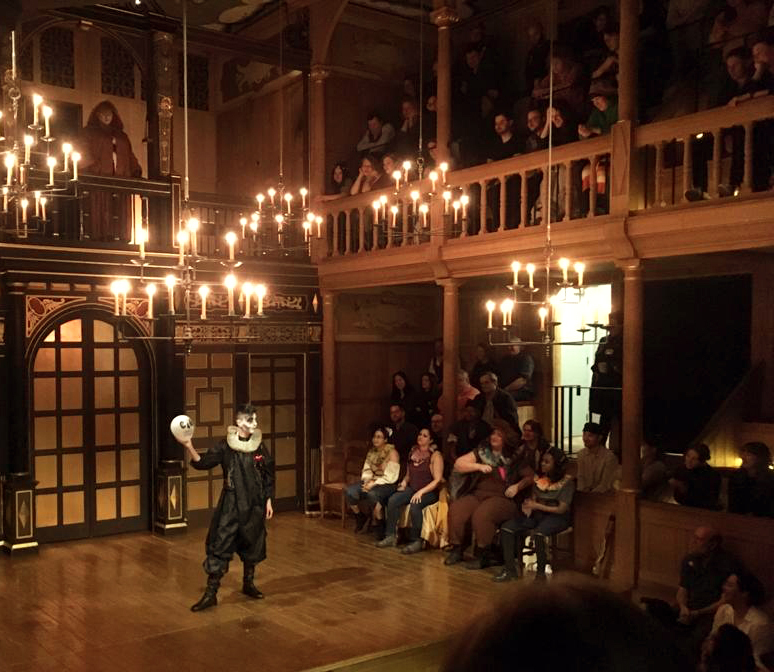 A drag artist wearing black doublet and hose, and holding a skull, stands in the candlelit Sam Wanamaker Playhouse.