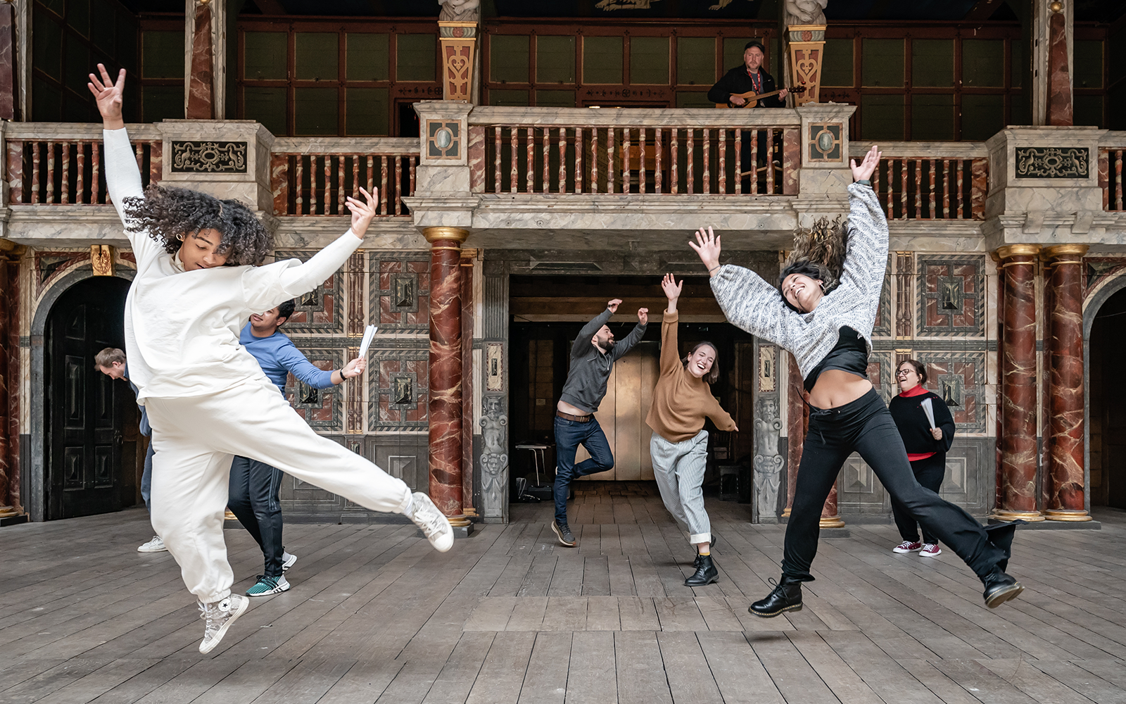 On an outdoor, wooden stage, a group of actors dance and jump in the air