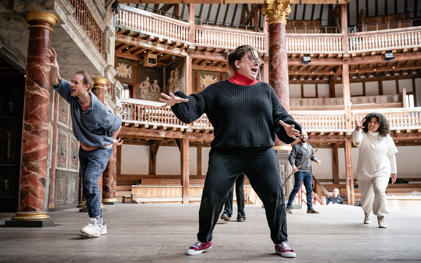 On the Globe Theatre stage, a group of actors are in the middle of a scene, gesturing and mid-movement