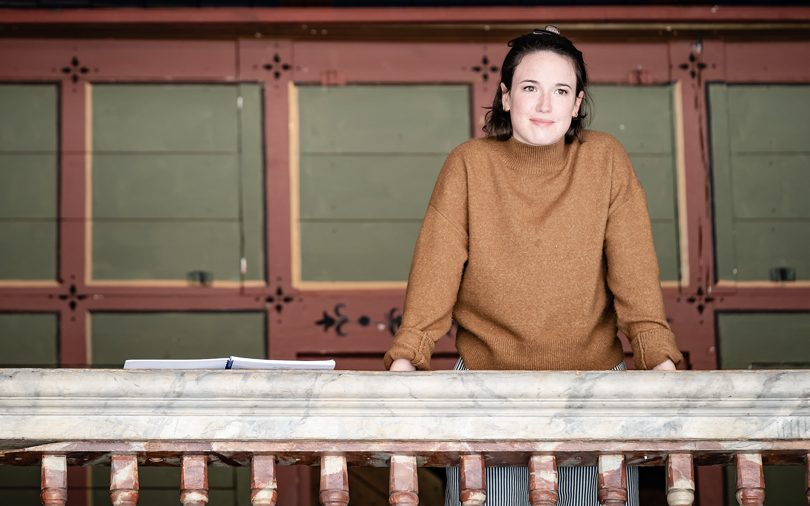An actor on a balcony wears a brown jumper and looks onwards to something in the distance