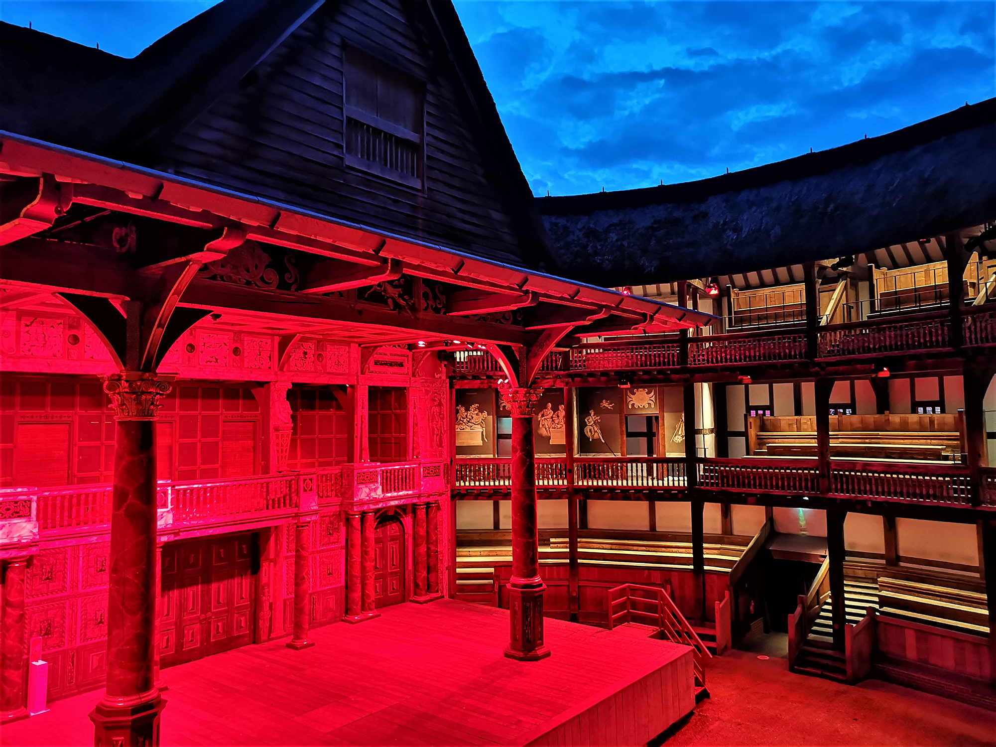 The stage of the Globe Theatre is lit by red lights.