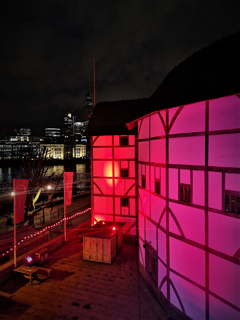 The normal white walls of the Globe Theatre are lit by red light.