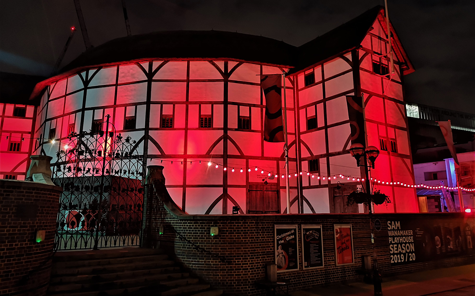 The Globe Theatre on bankside at night, lit by red light.