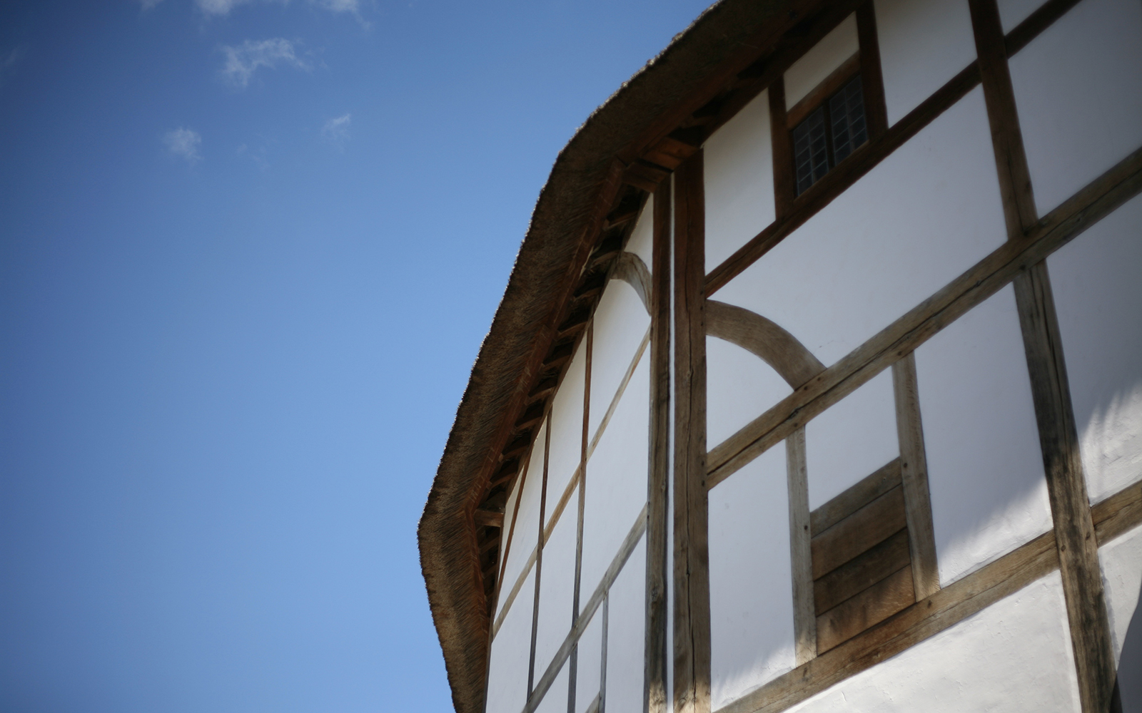 The exterior white wattle and daub timber walls of the Globe Theatre loom above, with a spring blue sky overhead