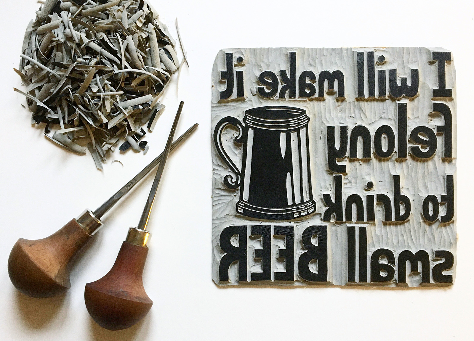 Carving tools lay next to a block with a print of a beer tankard and the text: I will make it felony to drink small beer, in reverse