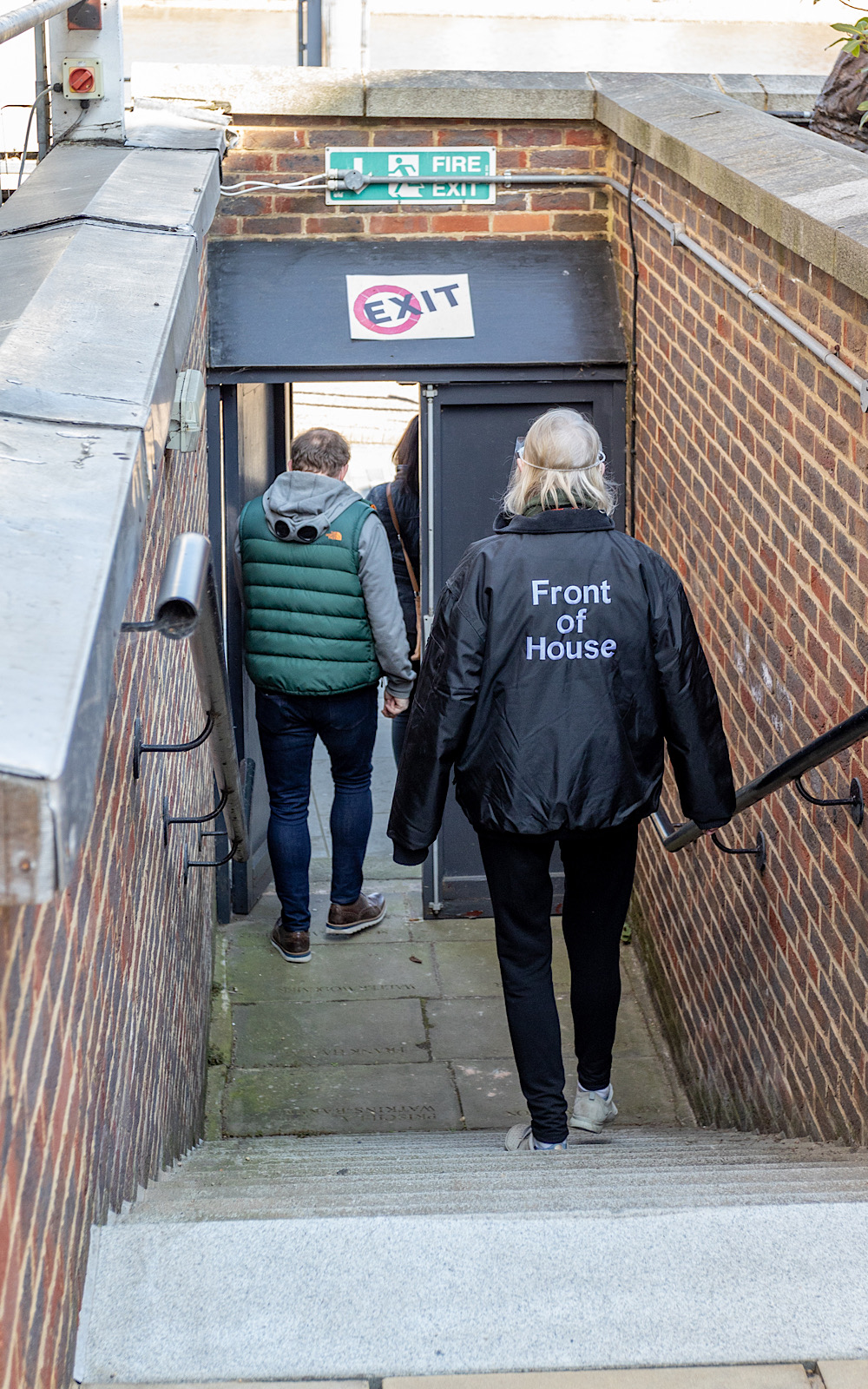 Two people walk down outdoor steps towards a sign that reads 'exit'