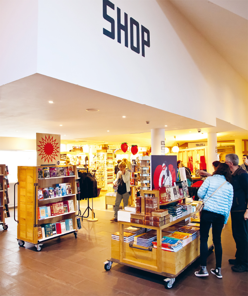 Customers browse a display of books in a shop.