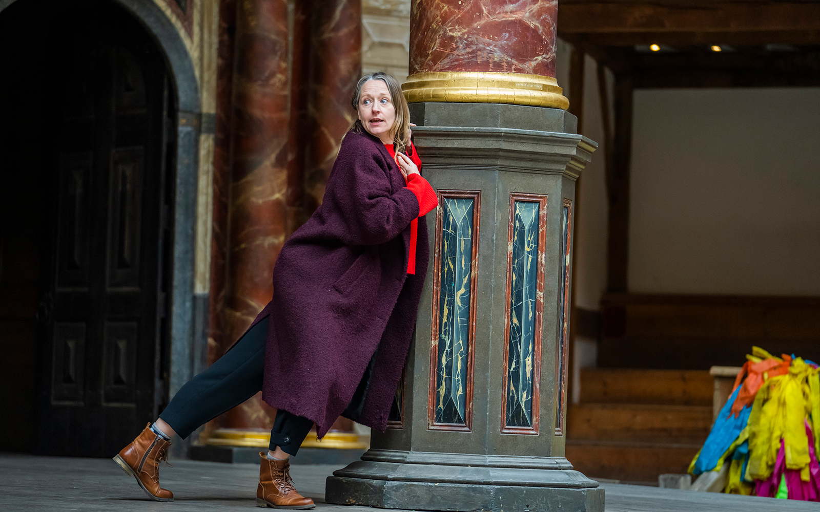 An actor wears a long, red coat and is leaning against a pillar on a stage