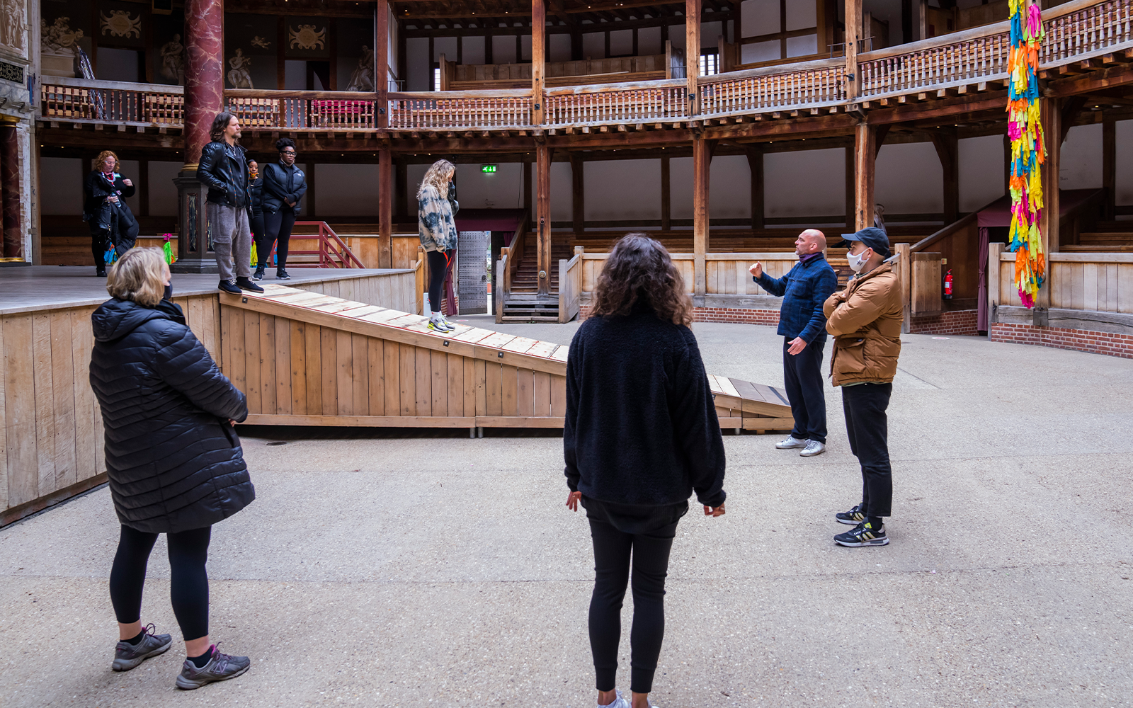 A group of actors stand on the edge of a wooden stage as members of the creative team, including the director, talk to them from the yard below