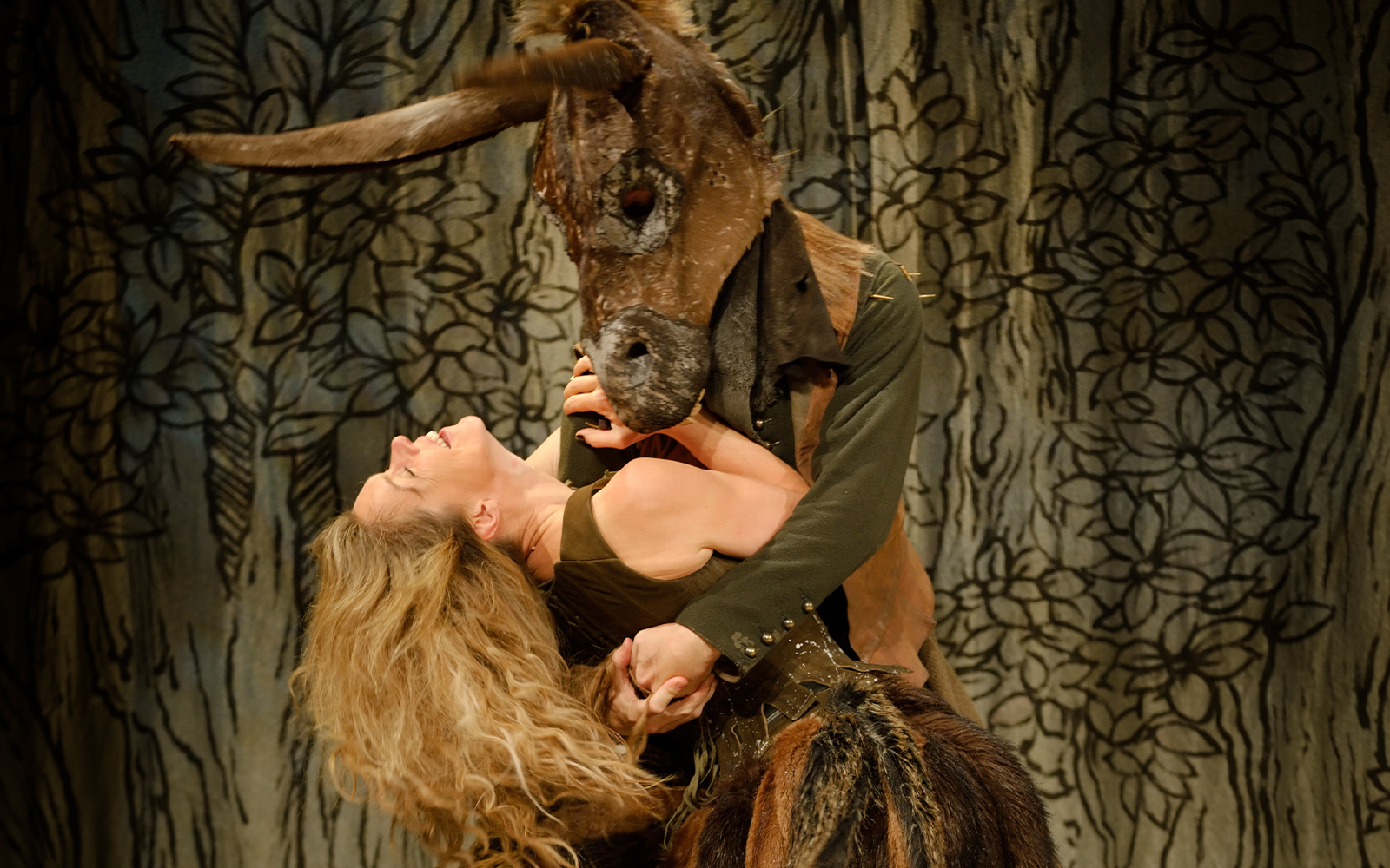 A person being dipped down by another person wearing a head of a donkey