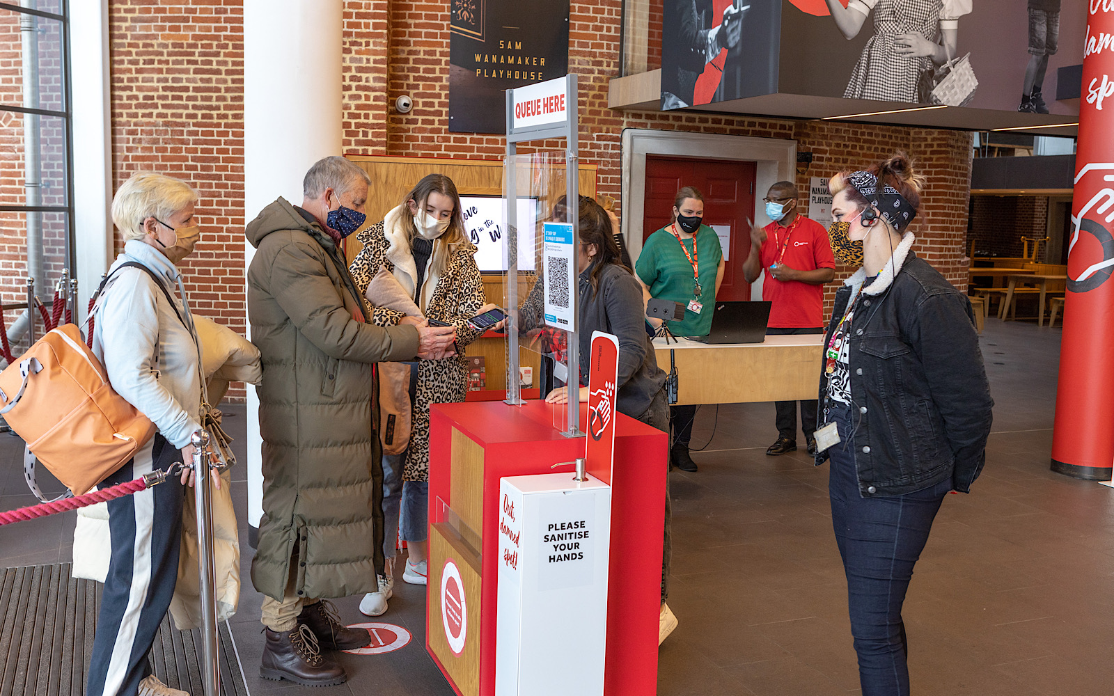 An audience member shows a ticket on their phone to a member of staff who stands behind a perspex stand