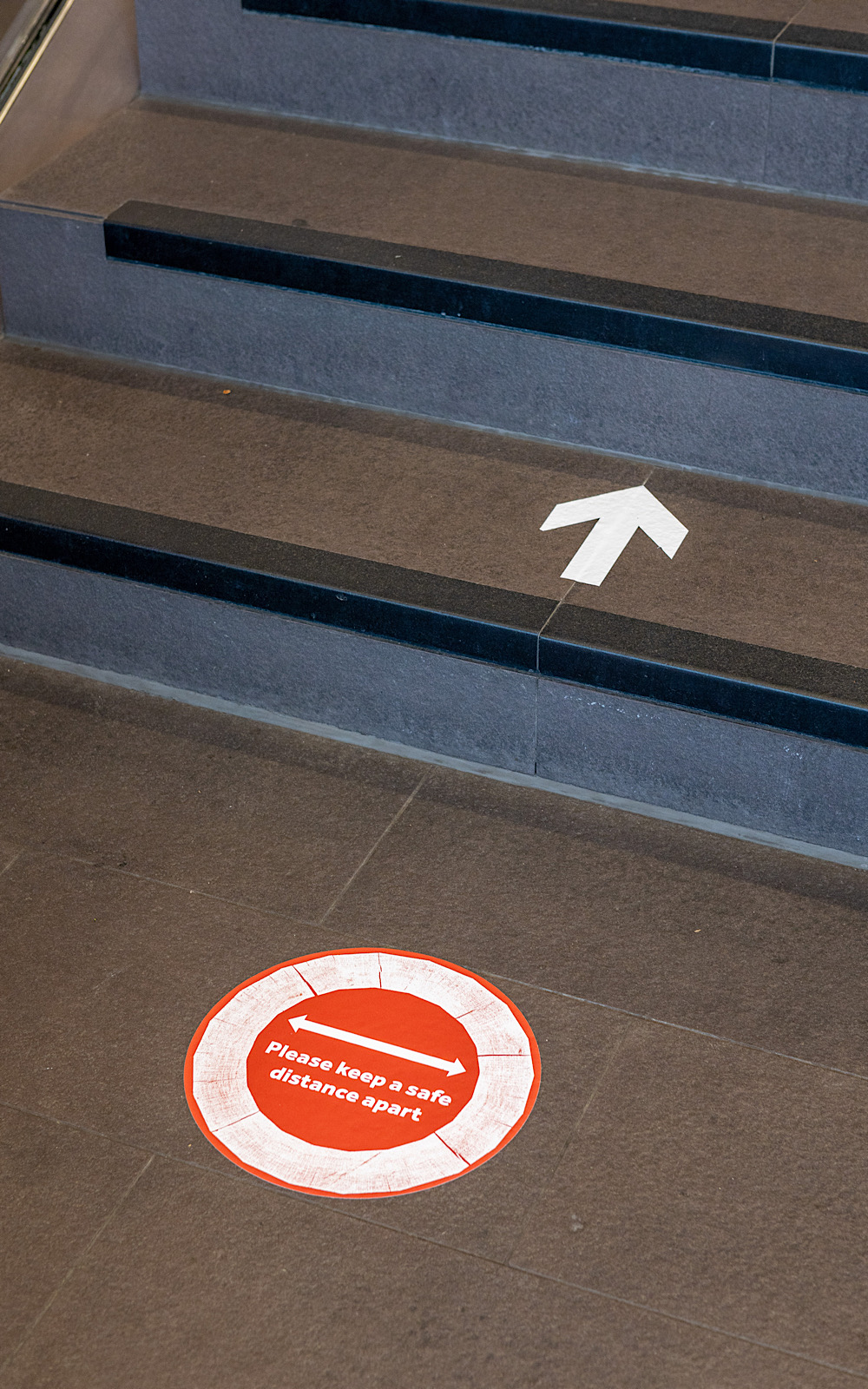 Stickers on a black floor show arrows and also notices to keep a safe distance from others
