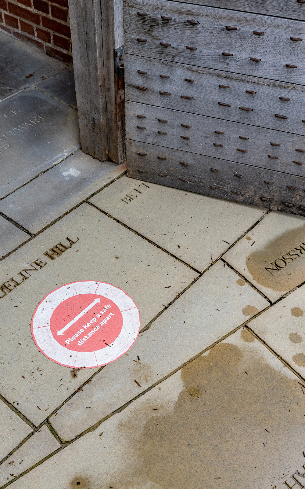 A red sticker on a stone floor reminds people to keep a safe distance apart from each other