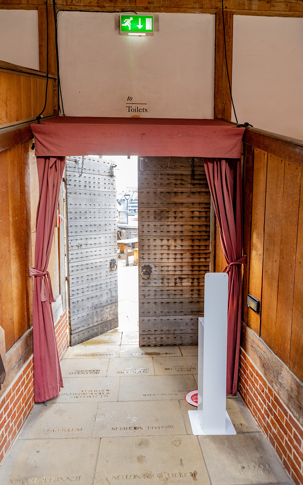From the inside of a wooden theatre, doors lead to the outside, they have red curtains around them and a hand sanitising station behind them