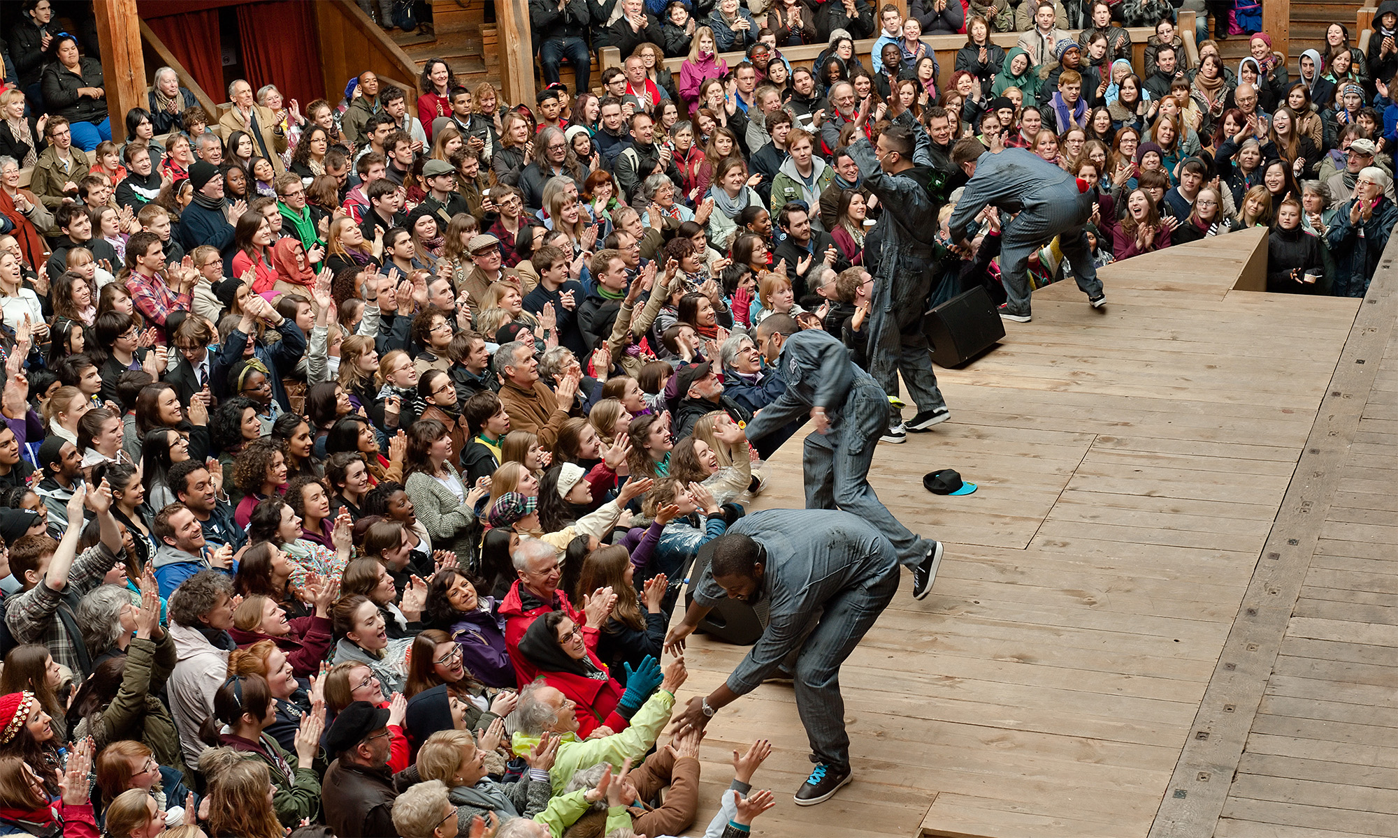 Four actors stand on the edge of a thrust stage, bending down to high five and hold the hands of audience members standing in the Yard in front.