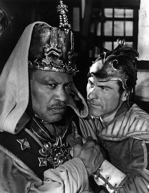 A black and white photograph of two actors, one leans in close, menacingly, towards the other.