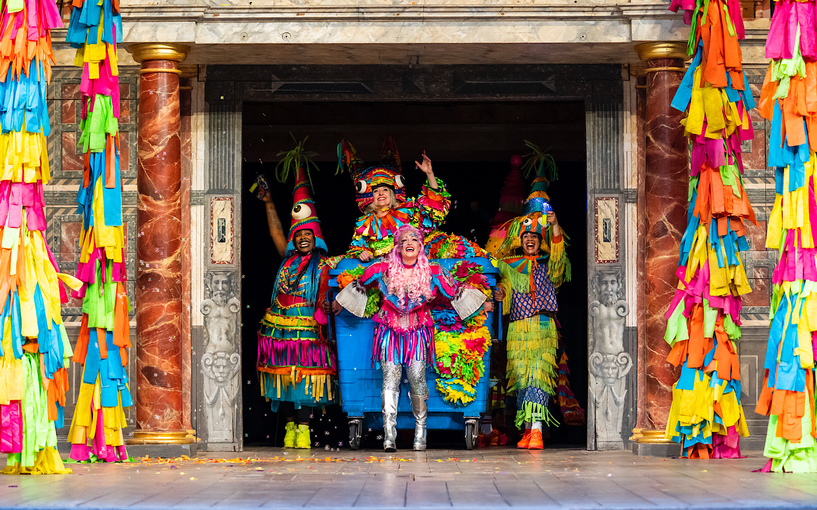 A group of actors bust onto the stage through doors, they are all dressed in bright colours and drag a blue wheelie bin which an actor sits on top of