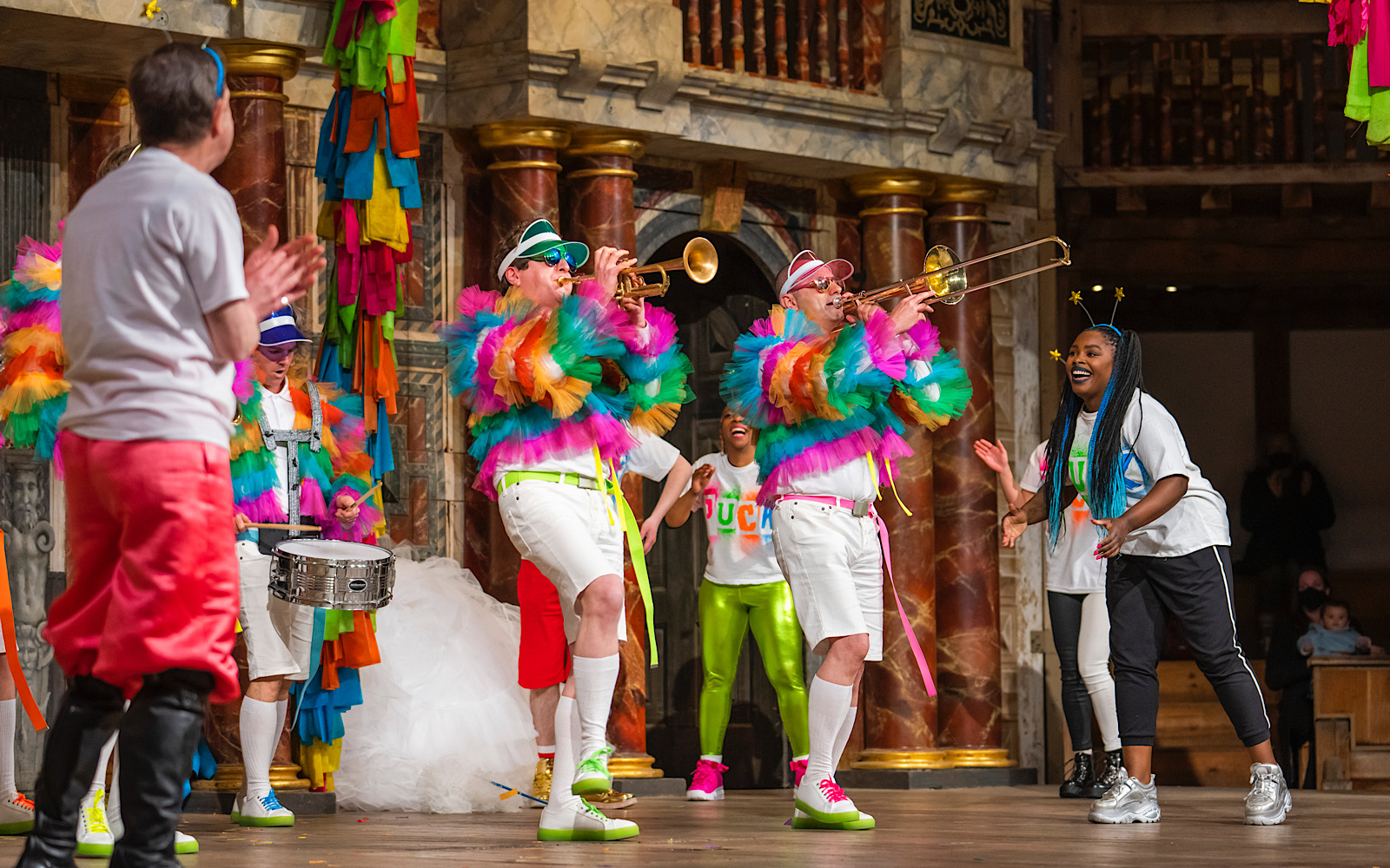 A group of musicians perform on stage in brightly-coloured jackets whilst other actors dance and smile around them