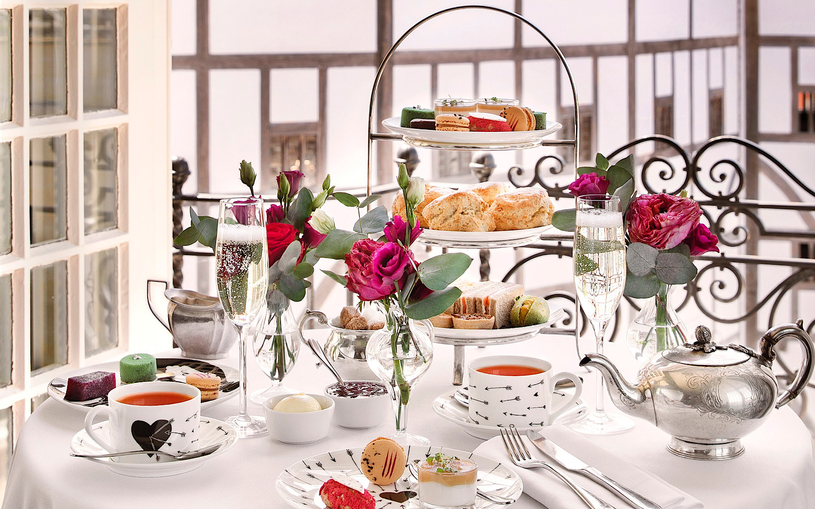 A lavish table set-up of afternoon tea shows tea, cakes and intricate crockery