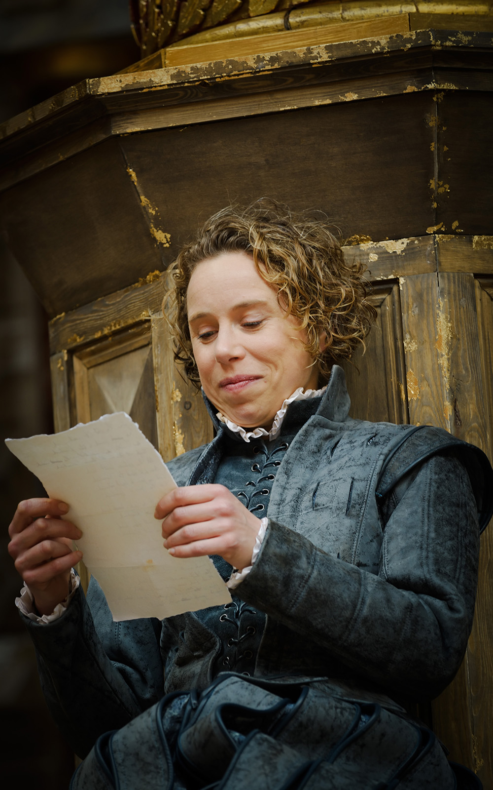 An actor with short curly hair and wearing a doublet and hose sits reading a poem on a sheet of paper, smiling.