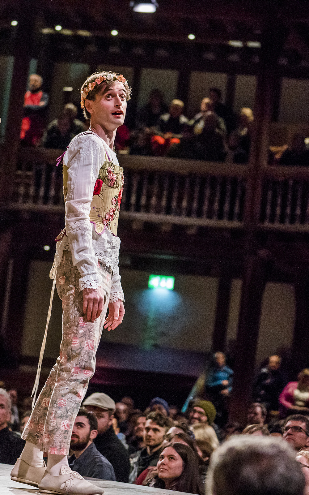 An actor wearing floral embroidered trousers and corset, over a white undershirt, looks over their shoulder, as audiences watch on.