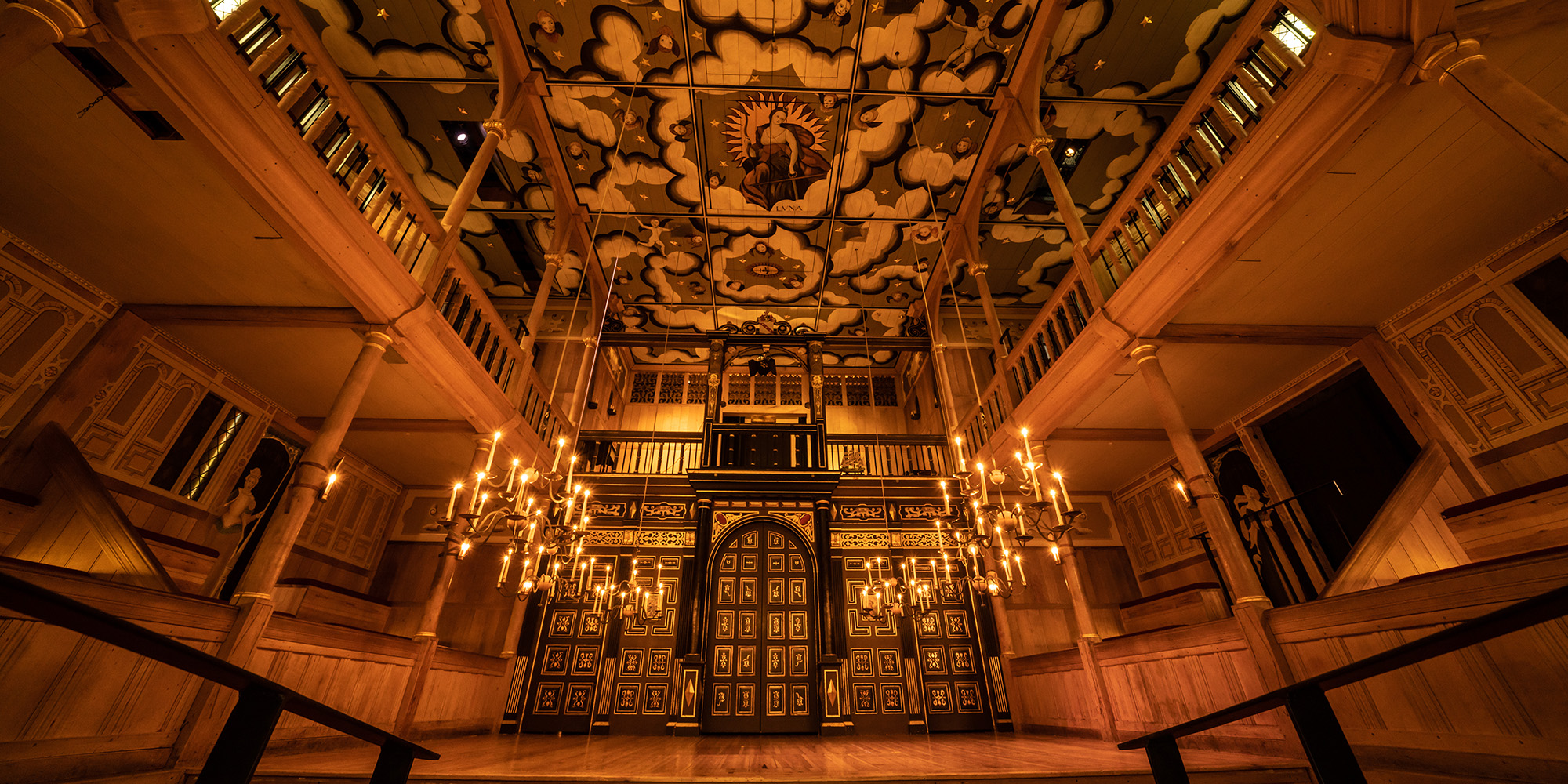 A wide angled shot of the Sam Wanamaker Playhouse with its ornate painting ceiling depicting the Goddess Luna and clouds, hanging candelabra, and panelled painted doors.