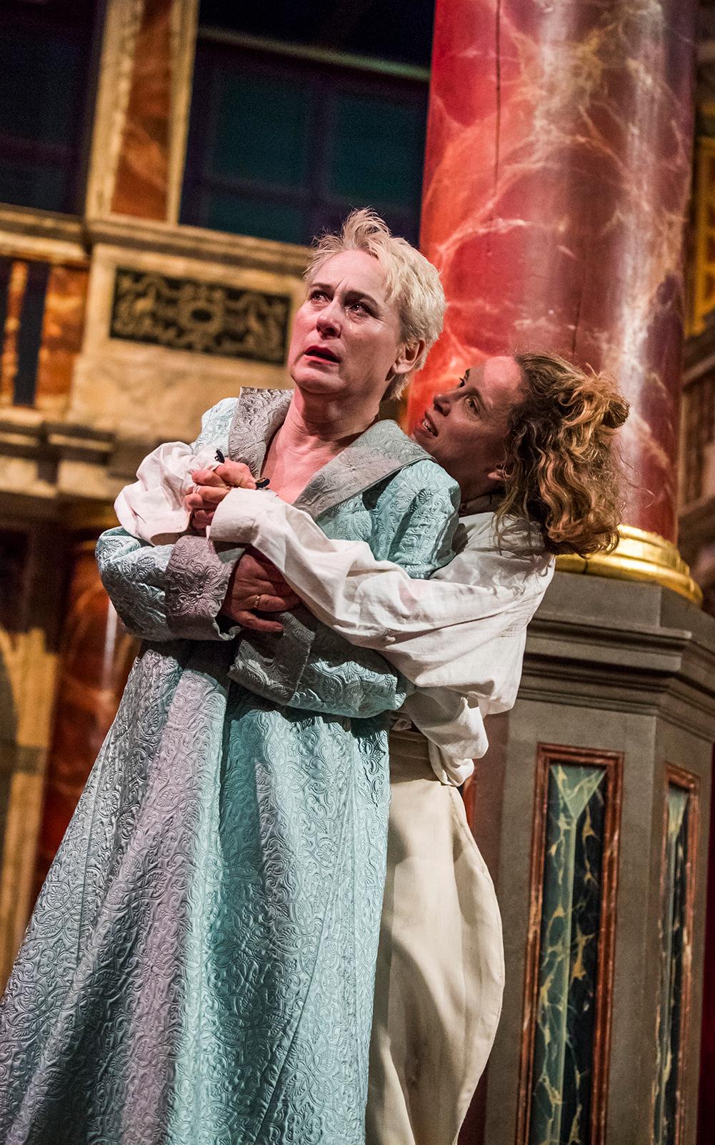 Hamlet standing behind Gertrude with arms around her